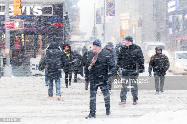 People seen crossing the road during snow storm in Times Square New York city is under heavy snow storm as a giant winter bomb cyclone walloped the...