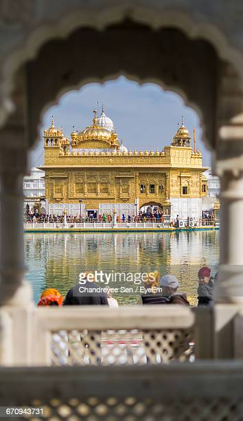 people seen from archway at golden temple - amritsar stock pictures, royalty-free photos & images
