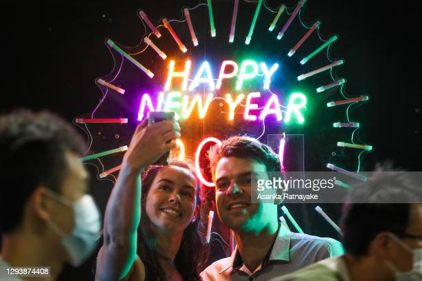 People seen having their photo taken in front of a neon Happy New Year sign as people wearing masks walk past during New Year's Eve celebrations on...
