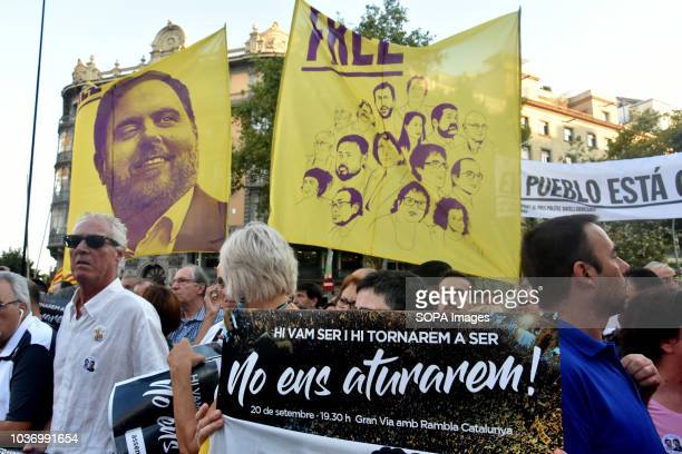 People seen holding banners as they gather at the Economy headquarters during protests in support of Catalonia's independence and commemorate the...
