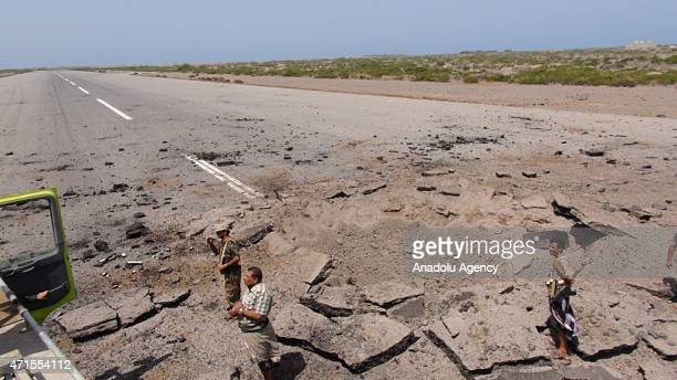 People seen near a crater left by the air attacks of Saudiled coalition at Hodeidah International Airport in Hodeidah Yemen on April 29 2015