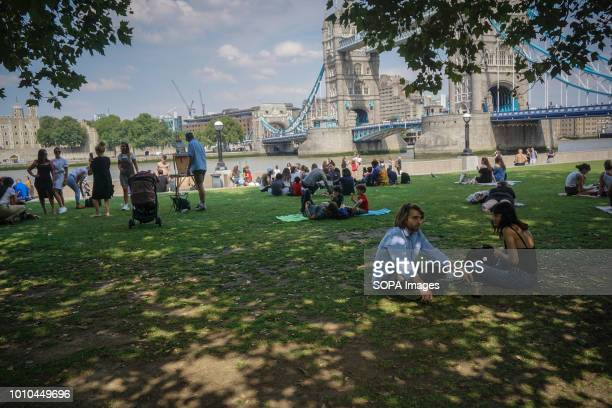 People seen relaxing under a tree shade during a warm day Another heat wave is scheduled to hit parts of the UK this weekend