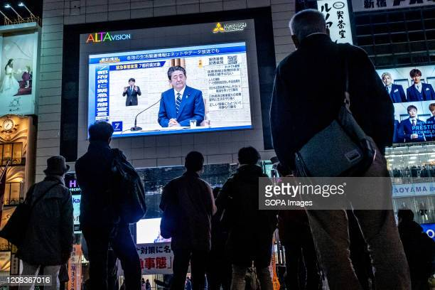 People seen standing in fron of a large television screen as the Japanese Prime Minister Shinzo Abe speaks at a press conference and addressing the...