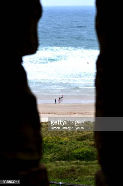 People Seen Through Cave On Shore At Beach