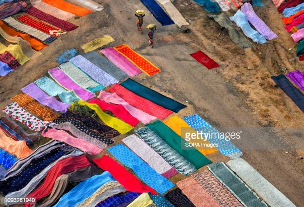 People seen walking through the colourful clothes spreaded on the soil next to the river bank of Barakar in Jharkhand area The Dhobi Ghat of...
