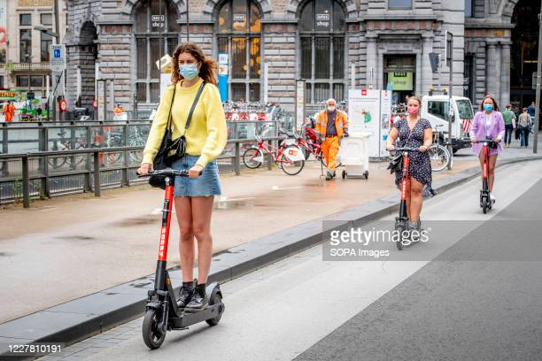 People seen wearing face masks as a preventive measure ride electric scooters on the street during the coronavirus crisis. The wearing of a face mask...