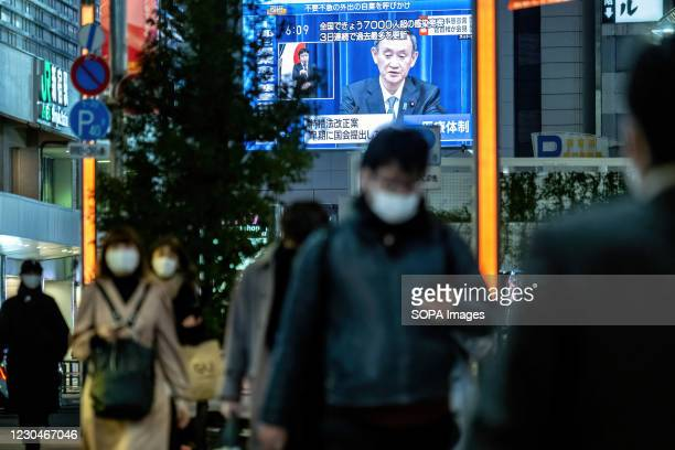 People seen wearing facemasks as a preventive measure against Covid-19 with a live broadcast of Japan's Prime Minister Yoshihide Suga declaring a...