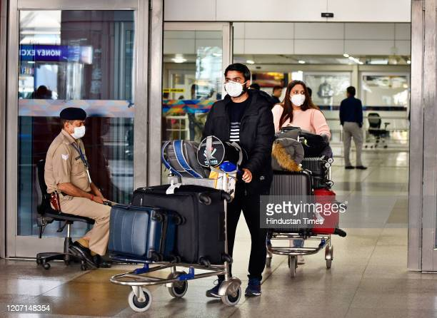 People seen wearing protective face masks as a precautionary measure amid rising coronavirus concerns at Indira Gandhi International Airport on March...