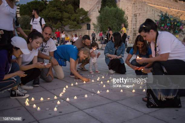 People seen with lighted up candles to form a peace dove during the event People gathered at the Panathenaic Stadium in Athens to celebrate the...