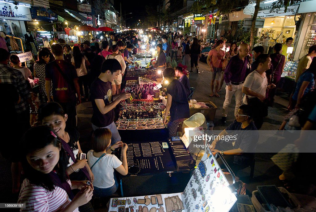 People select goods at Chiang Mai Sunday Market on November 25, 2012 in Chiang Mai, Thailand. The Chiang Mai Sunday Market, also called walking Street Market, is held from 4:00 pm until midnight and starts at Thapae Gate, running along the length of Ratchadamnoen Road through the heart of the Old City and is a Chiang Mai institution. Many of the stallholders have personally made the items they sell and the many hand crafted objects are a testimony to the skills and inventiveness of local people, which attracts local citizens and foreign tourists.