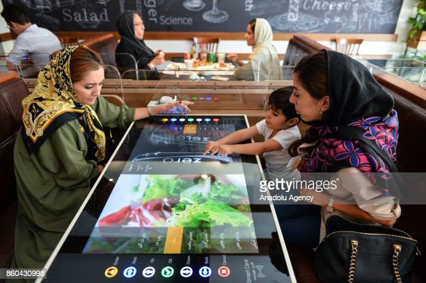 People select their food served by robot waiter which moves on rail system placed between tables at the first robotic restaurant 'RoboChef' in Tehran...