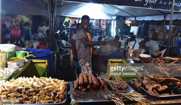 People sell food during the Panafrican Film and Television Festival whose organisers expect more than 100,000 visitors, on February 27, 2017 in...