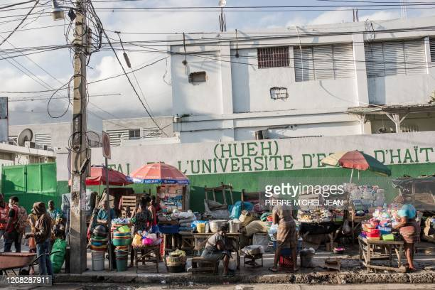 People sell merchandise near the State Hospital in downtown Port-au-Prince on March 26, 2020. - On March 19, President Jovenel Moise announced a halt...