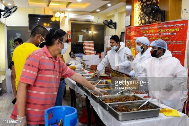 People selling Iftar meals to customers while wearing protective suits as a preventive measure during Ramadan amidst Coronavirus crisis. The...