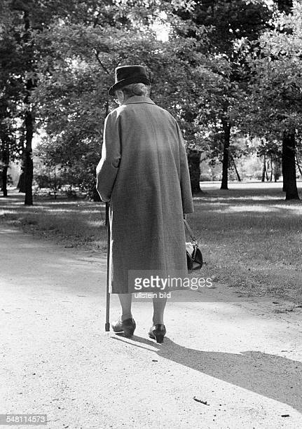 people senior older woman walks through the park walking stick coat hat aged 70 to 80 years