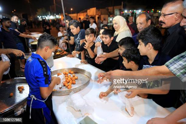 People serve dessert as part of the holy month of Muharram commemorations in Baghdad Iraq on September 19 2018 Ashure or Noah's Pudding dessert...