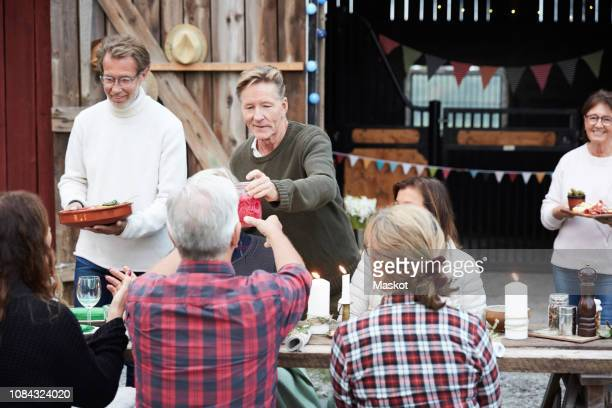 people serving food and drinks at dining table against barn during dinner party - noord europa stockfoto's en -beelden