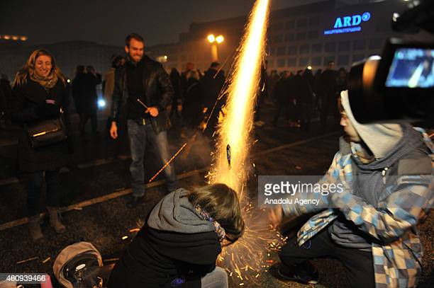 People set off firework near the Brandenburg Gate during the welcoming ceremony for the new year in Berlin Germany on January 1 2015