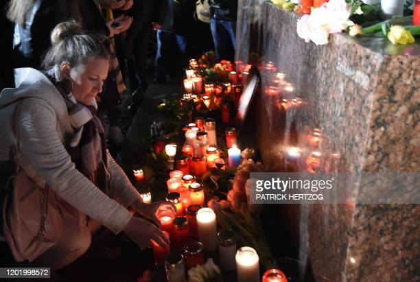 People set up candles during a vigil a central place in Hanau near Frankfurt am Main western Germany on February 20 after at least nine people were...