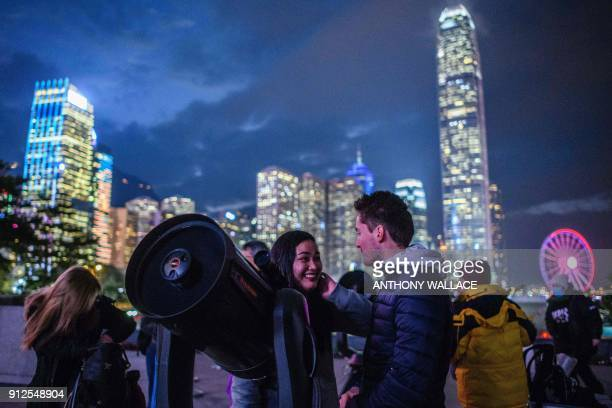 People set up telescopes near Victoria Harbour in the hope of seeing a 'supermoon' on a cloudy evening in Hong Kong on January 31 2018 Skywatchers...