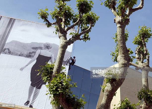 People set up the official poster of the Cannes' film festival 62nd edition on the Festivals' palace facade on May 11 2009 in Cannes south eastern...