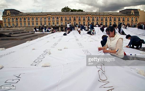 People sew white cloths with names of victims of the Colombian conflict painted in ash at the Bolivar square in Bogota on October 11 2016 Colombian...