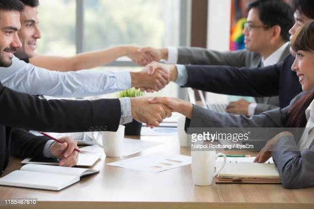 people shaking hands on table - respect stock pictures, royalty-free photos & images