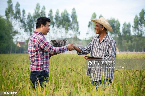 people shaking hands while standing on agricultural field - handshake stock pictures, royalty-free photos & images