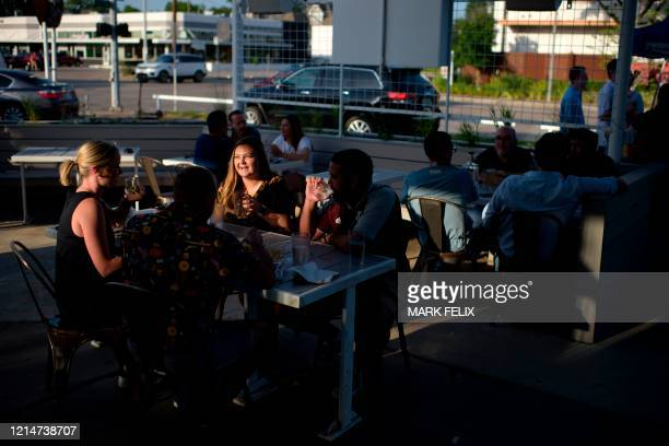 People share a laugh over drinks on the patio of Eight Row Flint in Houston Texas on May 22 amid the novel coronavirus pandemic