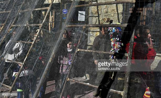 People shelter behind a net as they wait a man representing the Jarrampla to run through the streets beating a drum in Piorna on January 19 2017...