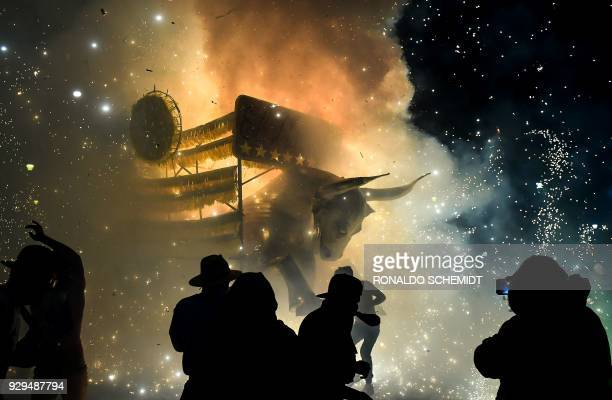 TOPSHOT People shelter from fireworks before the traditional 'torito' made of paper wood and fireworks during celebrations of San Juan de Dios in...