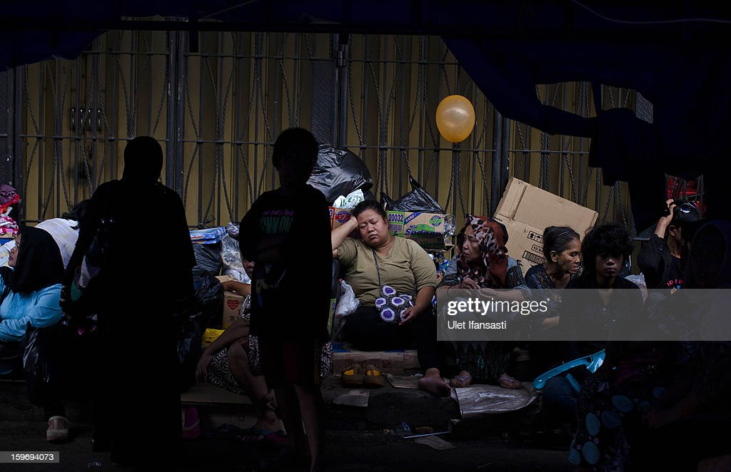 People shelter from floodwaters amongst their belongings in East Jakarta district on January 18, 2013 in Jakarta, Indonesia. According to the National Disaster Management Agency, about 50 percent of the capital is under water following the floods which have so far claimed eleven lives and displaced thousands of Indonesians.