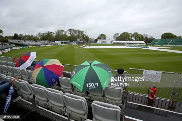 People shelter from the rain as groundsmen work on the wet pitch at Malahide cricket club in Dublin as the start of play is delayed on the first day...