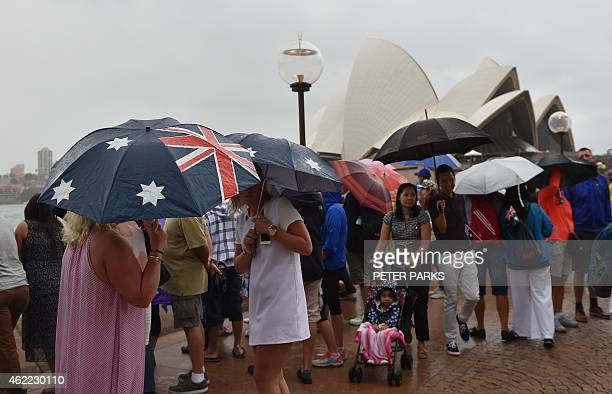 People shelter from the rain at Sydney Harbour as Australians celebrate Australia Day in Sydney on January 26 2015 Australian Prime Minister Tony...