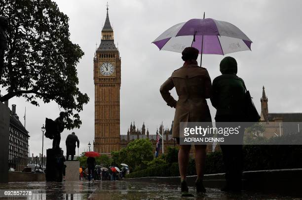 TOPSHOT People shelter from the rain beneath an umbrella as they observe a minutes' silence near the Elizabeth Tower commonly referred to as Big Ben...