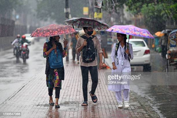 People shelter from the rain beneath umbrellas during a rainfall on Farmgate street. Heavy monsoon downpour caused extreme water logging in most...