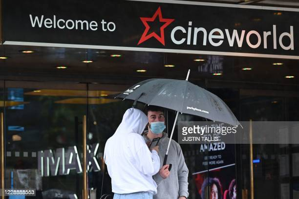 People shelter from the rain under an umbrella outside a cineworld cinema in Leicester Square in central London on October 4 2020 Cineworld is set to...