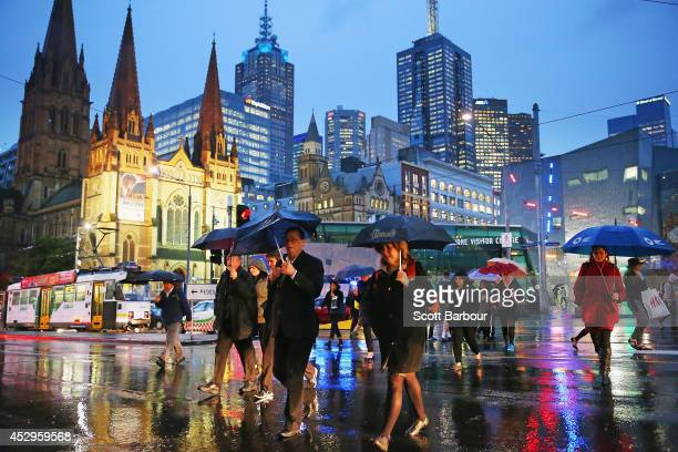 People shelter from the rain under umbrellas as they cross the road from Federation Square on July 31 2014 in Melbourne Australia Temperatures...