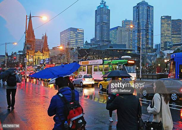 People shelter from the rain under umbrellas as they walk towards Federation Square on July 31 2014 in Melbourne Australia Temperatures dropped and...