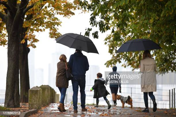 People shelter from the rain under umbrellas during a downpour in Greenwich Park, south-east London on October 3, 2020. - Heavy rain is lashing parts...