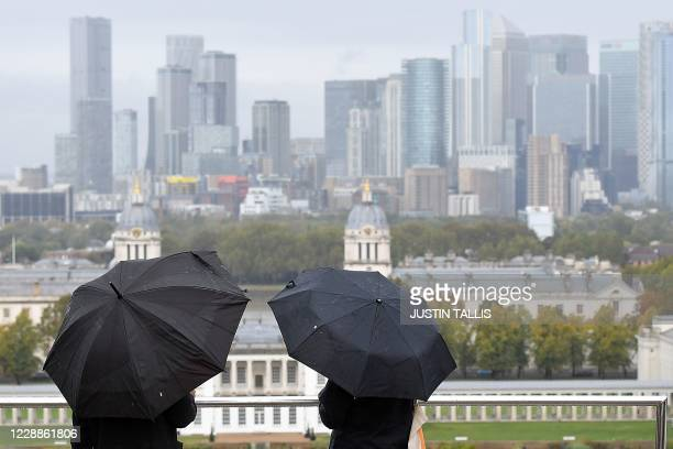 People shelter from the rain under umbrellas looking out at the view of the London city skyline during a downpour in Greenwich Park, south-east...
