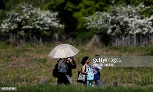 People shelter from the sun beneath an umbrella as they walk in the sunshine in Richmond Park in south west London on May 7 2018 Temperatures on...