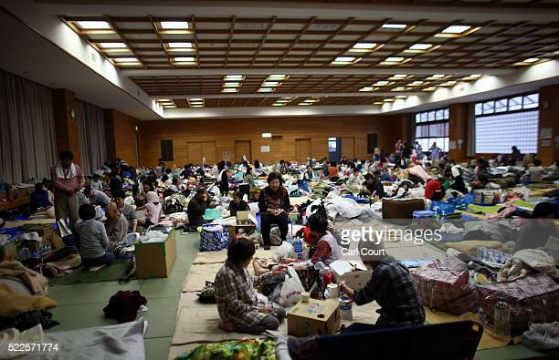 People shelter in a gymnasium used as an evacuation centre following an earthquake, on April 20, 2016 in Mashiki near Kumamoto, Japan. As of April...