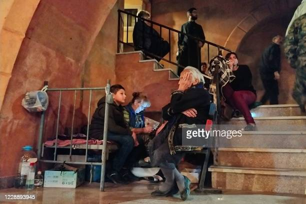 People shelter in the basement of the main church of the breakaway Nagorno-Karabakh region's main city of Stepanakert on October 4 during the ongoing...