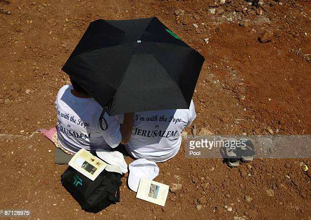 People shelter themselves from the sun as they wait for the arrival of Pope Benedict XVI to arrive to lead a mass at the Garden of Gethsemane at the...