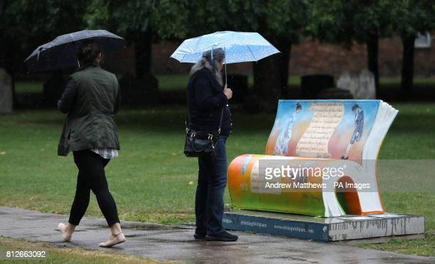 People shelter under umbrellas as they look at a Jane Austen inspired bench outside Winchester Cathedral which is part of the 'Sitting with Jane' art...