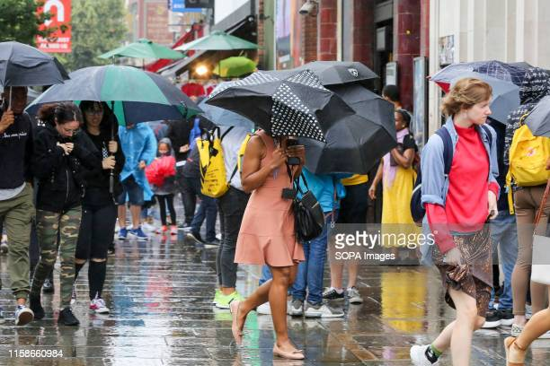 People shelter under umbrellas in London as rain falls after recent warm weather