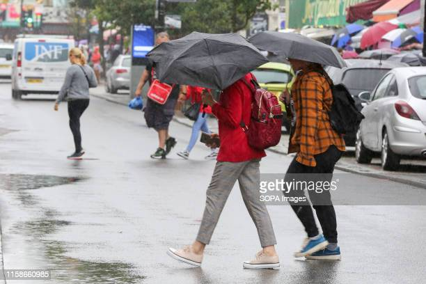 People shelter under umbrellas in London as rain falls after recent warm weather.