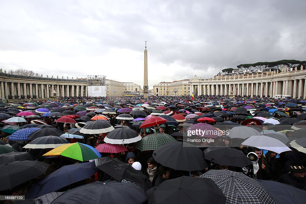 People shelter under umbrellas while they wait in St Peter's Square for news on the election of a new Pope on March 13, 2013 in Vatican City, Vatican. Pope Benedict XVI's successor is being chosen by the College of Cardinals in Conclave in the Sistine Chapel. The 115 cardinal-electors, meeting in strict secrecy, will need to reach a two-thirds-plus-one vote majority to elect the 266th Pontiff.