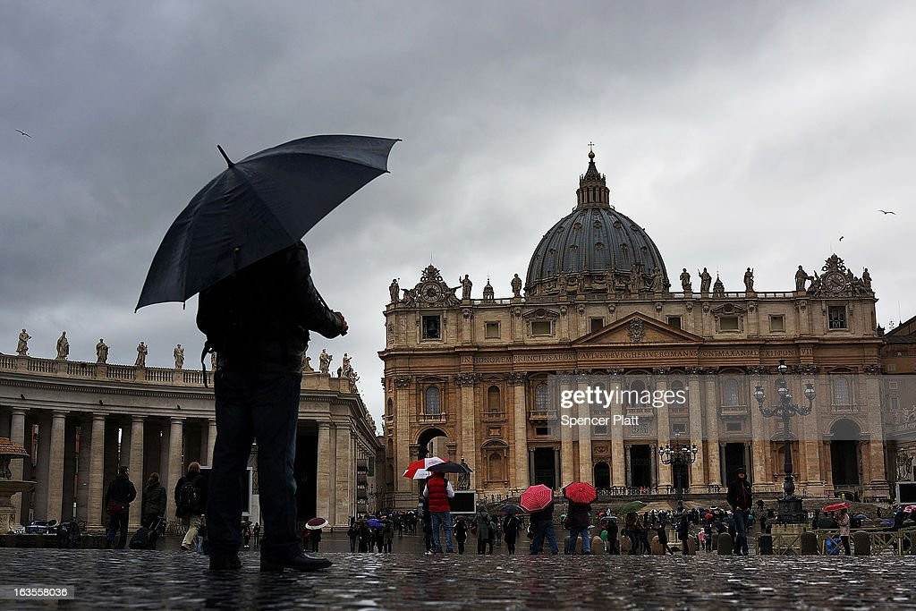 People shelter under unbrellas as they wait in St. Peter's Square on March 12, 2013 in Vatican City, Vatican. Pope Benedict XVI's successor is being chosen by the College of Cardinals in Conclave in the Sistine Chapel. The 115 cardinal-electors, meeting in strict secrecy, will need to reach a two-thirds-plus-one vote majority to elect the 266th Pontiff.